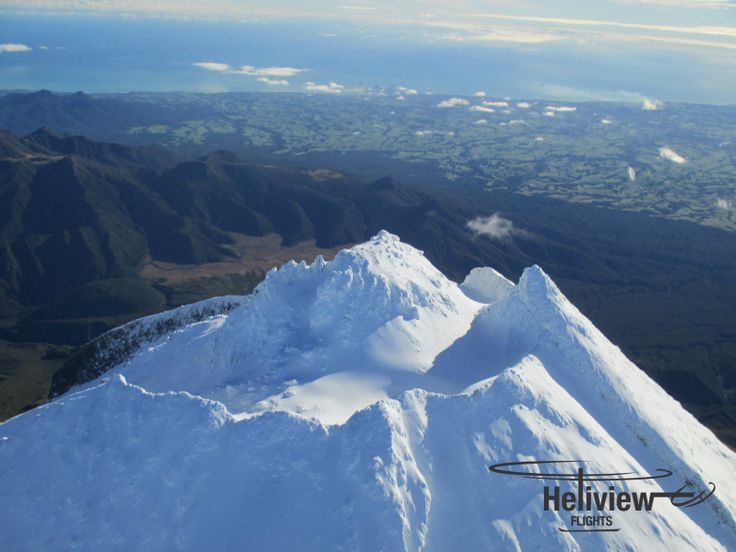 A close-up of the snowy peak of Mt Taranaki. Sharks Tooth on the right, the summit in the centre, looking down at the Ahukawakawa Wetland and Pouakai Range.