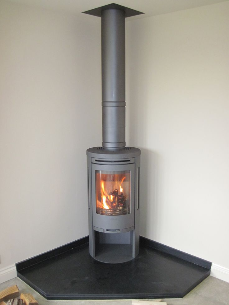 Contura 585 wood burner. Poujoulat flue sprayed the same colour. Black granite corner hearth with granite skirting boards cut to meet existing wooden skirting board. Corner-contained, clean and classy look.