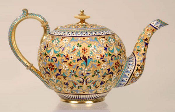 A Russian silver gilt and cloisonne enamel teapot, Gustav Klingert, Moscow, late 19th century. Of traditional form, the teapot is decorated with a scrolling floral and foliate motif between geometric pattern enamel bands against a gilded stippled ground. Turquoise enamel bead borders and ivory accents.