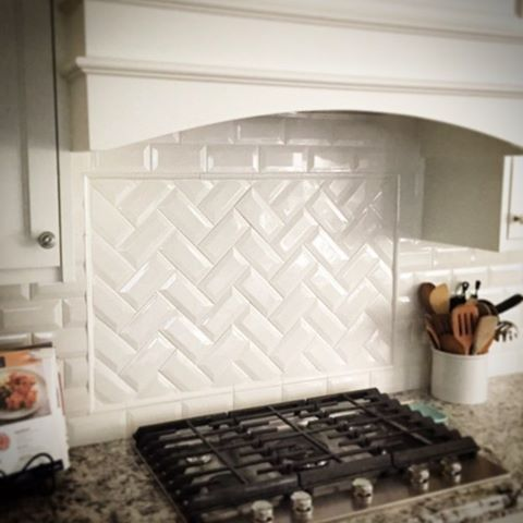 White Subway tile in a herringbone pattern for the…