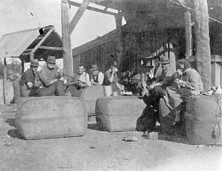Agricultural Workers Having a Tea Break Seated on Wool Bales, Australia, circa 1930   A group of agricultural workers having a tea break. They are seated on wool bales.