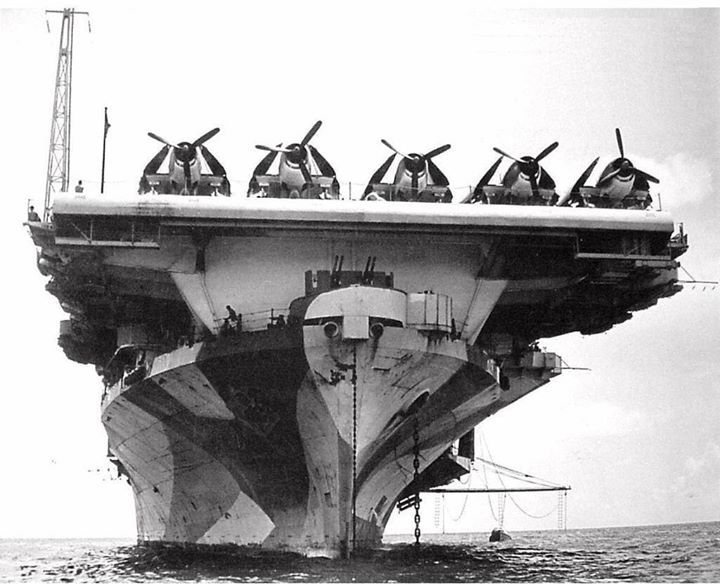 Bow on view of USS Hornet (Essex-class) at anchor in Berth X-12 Majuro Lagoon Marshall Islands 12 May 1944. Note F6F Hellcat fighters spotted on the flight deck.
