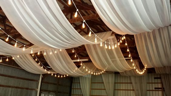 Ceiling draping in a barn. This makes a rustic wedding look perfect. See more wedding decor ideas and reserve your fav items from Nolan's Rental ASAP!