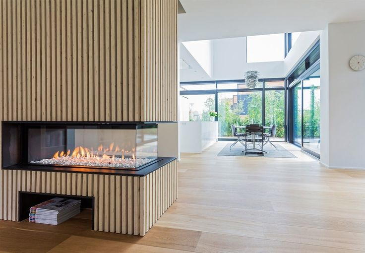 Nordic transparent gas fireplace in the living room surrounded by wooden slats.