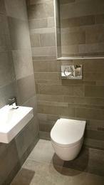 Toiletruimte wordt meer dan het kleinste kamertje... Door gebruik van warm grijs in verschillende afmetingen wordt het het meest bekeken kamertje van het huis...Prachtig en tijdloos die grijstinten. Te zien bij Astra Badkamers en Tegels te Woerden