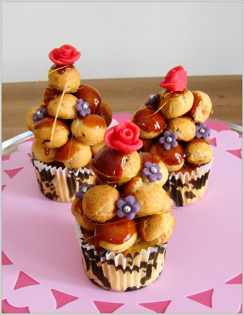 Croquembouche cupcakes : Vanilla cupcake base filled with chocolate cream pastry topped with mini choux pastries also filled with chocolate cream pastries. The tower is clued together with a caramel glaze with a bit of caramel sugar spun around the tower. Decorated with handmade pink marzipan roses and violet marizpan flowers with silver balls. -- by Cupcakegalore via Flickr