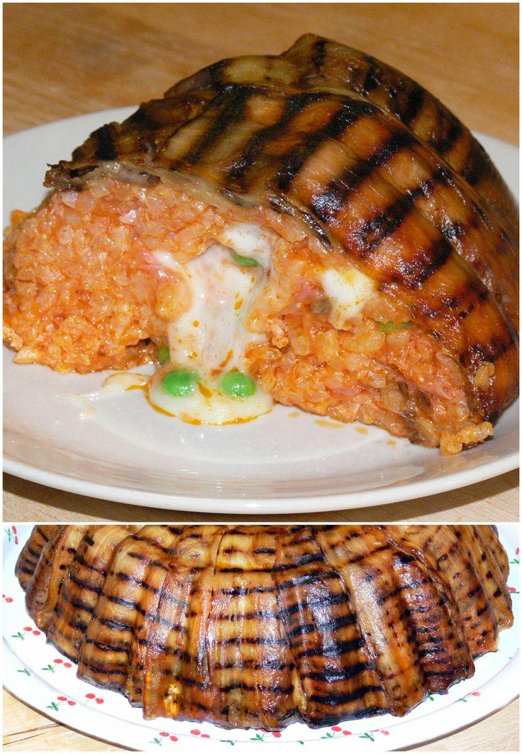 Sartù di riso al pomodoro con prosciutto, formaggio e piselli, avvolto in fette di melanzane