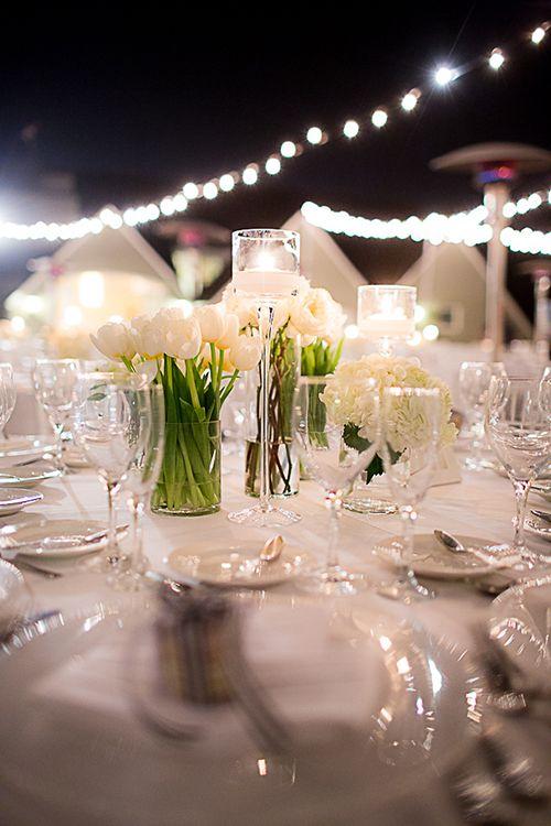 All-white centerpieces of hydrangeas, tulips, freesia, garden roses, and dahlias | @cloveandkin | Brides.com