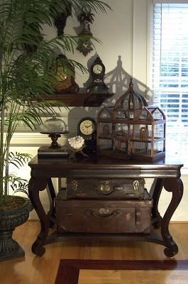Another dark birdcage, and luggage trunks along with old clocks and palms fit the theme well