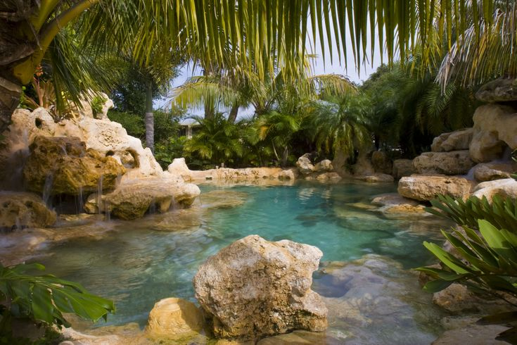 This custom lagoon pool by Lucas Lagoons included a white sand bottom with natural Florida limestone rocks and boulders set inside and outside the pool forming two multiple water features on opposite sides flowing into the pool.  Swimming under the water with the sand and limestone gave the feeling like you were swimming in a spring.  And the water being purified with an ionization system, used in every Lucas Lagoons swimming pool, guaranteed the natural fresh spring water feel.