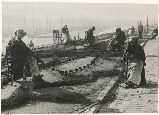Tweede haven, op de stoep van de Zeesluisweg repareren boetsters de netten. 1948 Nederlandsch Fotobureau #ZuidHolland #Scheveningen