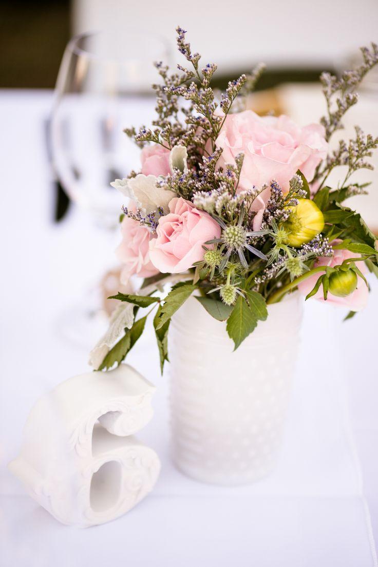 Blush and white wedding florals in vintage milk glass.