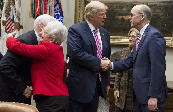 US President Donald Trump shakes hands with Representative Greg Walden (R), Republican of Washington and House Energy and Commerce Committee Chairman, alongside US Vice President Mike Pence (L), as he hugs Representative Virginia Foxx (2nd L), Republican of North Carolina and House Education and Workforce Committee Chairwoman, as they meet with House committee chairman about healthcare reform in the Roosevelt Room of the White House in Washington, DC, March 10, 2017. / AFP PHOTO / SAUL LOEB
