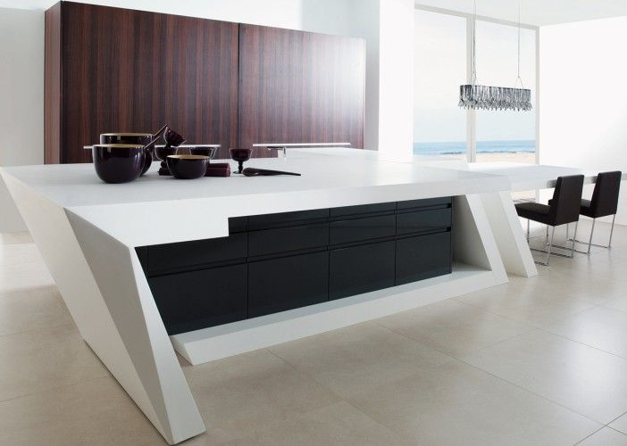 25mm thick doors finished in gloss/matt laquers and incorporating an integral handle machined into the profile of the door itself. Shown here complemented by Ukola veneered tall units and a unique KRION™ benchtop which slides out to unveil the sink and cooktop