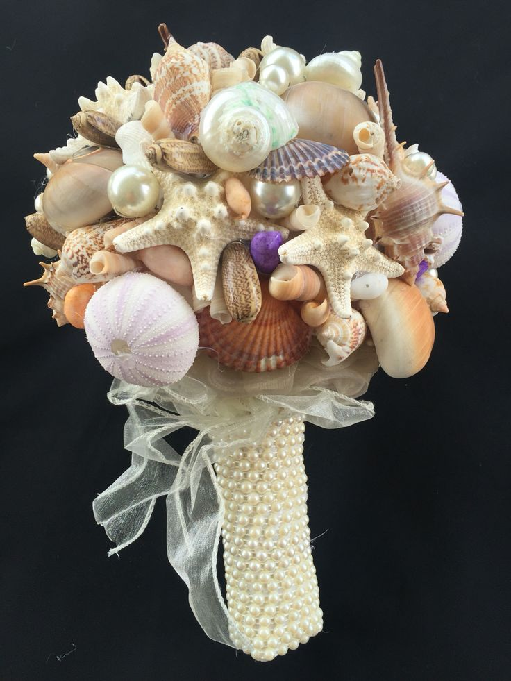 A stunning bouquet of natural seashells and shiny pearls makes this the perfect bouquet for any beach wedding. The pearl handle and organza skirt compliment the natural beauty.    All bouquets can be reproduced in the size and colour of your choice. Feel free to mix and match ideas to make your bouquet more individual. Corsage, MOB and Lapel pins are also available to match your colours. Contact leeann@bejewelledbridal.com.au for more information.
