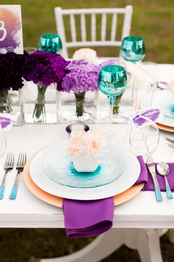 Table settings for a purple and teal peacock wedding
