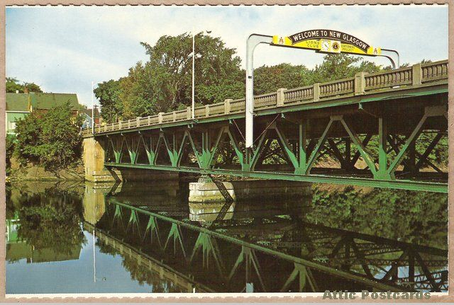 """Vintage chrome postcard of a river and bridge in New Glasgow, Nova Scotia, Canada. Shows a """"Welcome to New Glasgow"""" and Lions Club sign on the bridge, the latter promoting a """"Centennial Project"""". Photo by Alex Pelett."""