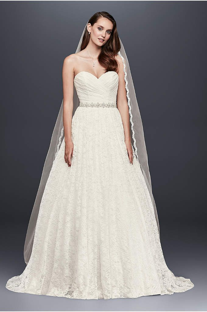 The picture of modern elegance, this gown features a plunging, sequined lace illusion bodice with a timeless button back. The fluid crepe skirt falls into a beautiful column with an inset train. Gali
