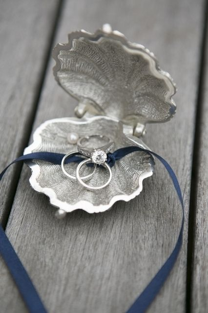 Silver and pearl clam ring holder for a beach wedding. Photography by samanthamelanson.com