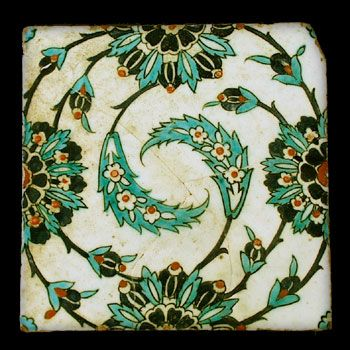 Ottoman Turkey or Syria. A stone paste tile, the very pale green ground decorated in underglaze cobalt-blue, turquoise and bole red with lotus heads midway on each side all around a central pair of swirled saz leaves. First half of the 16thcentury