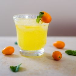 A refreshing summer rum drink with kumquats and mint.