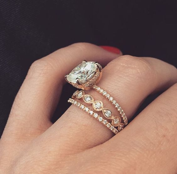 14k yellow gold engagement ring with a 5 carat cushion cut moissanite center and stackable bands