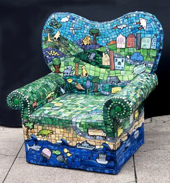"""Connie Levathes fabricated this mosaic garden chair using recycled polystyrene, cement, and fiberglass mesh. Scraps of stained glass were painted and fired, each depicting images inspired by children's artwork from one of San Francisco's public schools. This chair was featured in """"500 Chairs"""" from Lark Books."""