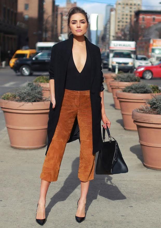 Confiira o estilo da fashionista americana Olivia Culpo, de calça culottes, ou pantacourt, suede, body decotado e sobretudo preto, completando com scarpin e bolsa da mesma cor.