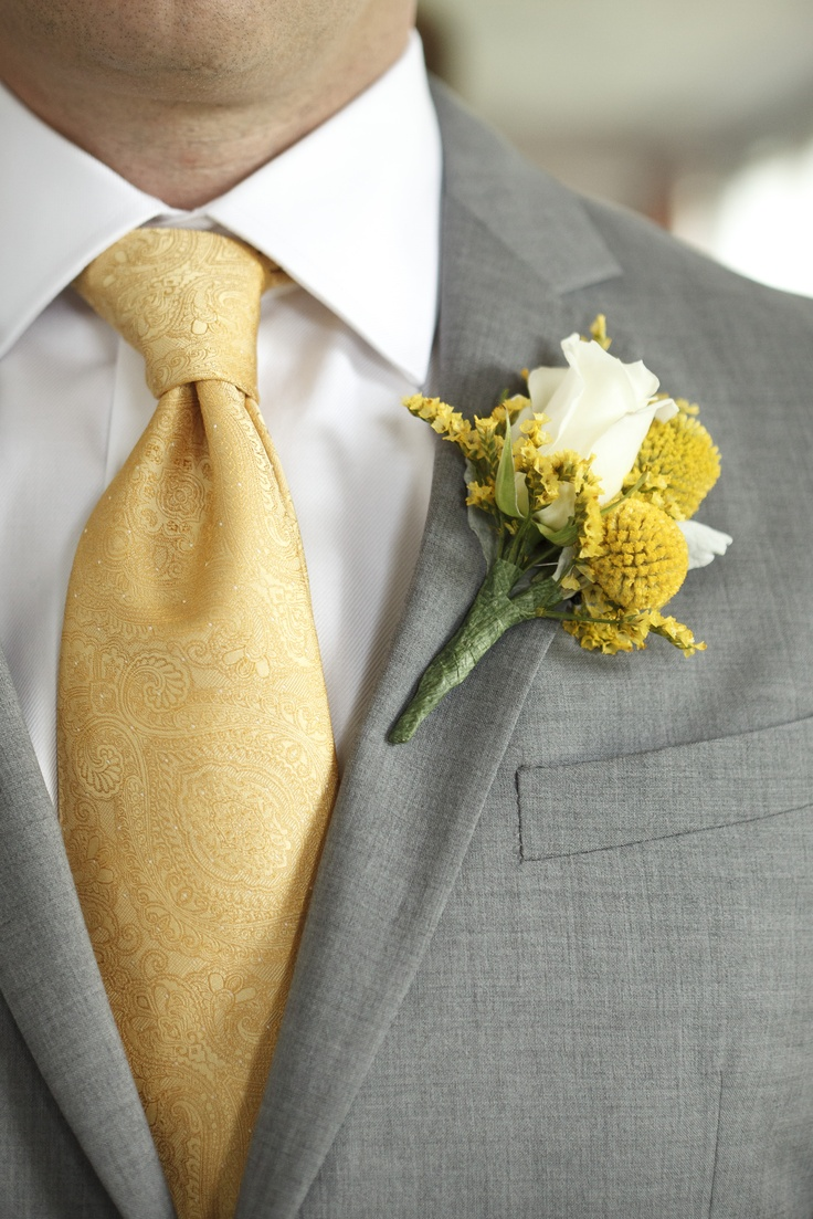 Yellow and gray were my wedding colors. My groom wore a gray suit with a yellow tie for our garden wedding. His boutonniere was done by Sky's the Limit florist with yellow billy balls and a white rose.