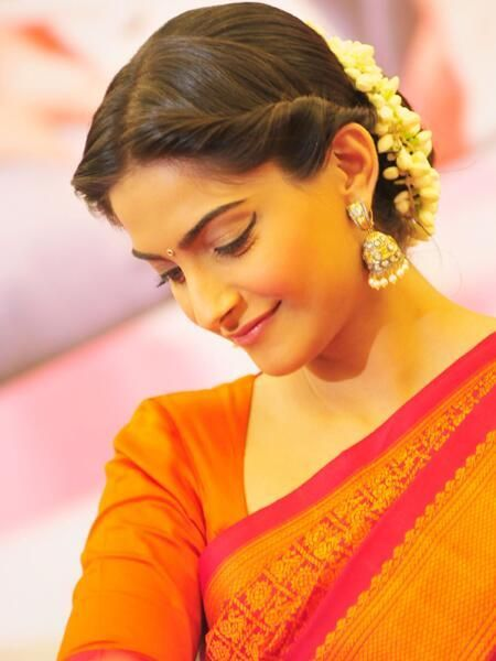 Sonam Kapoor looks gorgeous in a silk saree and an updo with gajra. Bollywood fashion.