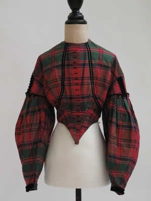 1860s Red, Blue & Green Plaid Bodice make star  1865 -1870 Red, blue and green plaid womans bodice [Cotton]  Overview: This 1860s blue and green plaid bodice is made from lightweight silk fabric. It is trimmed with black cotton velvet ribbon. The lining is glazed linen. Some seams on this garment have been machine stitched, but most of the bodice has been made and trimmed by hand.