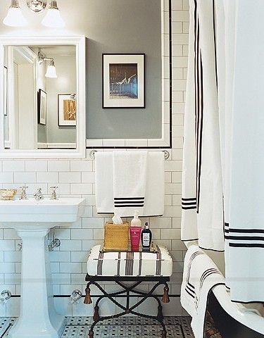 classic bathroom.  gray walls, basketweave tile floors, pedestal sink, and vintage deep soaking tub.  Gorge.  Domino