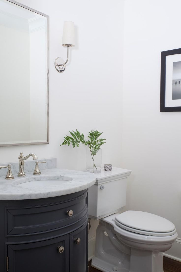"""In small bathrooms, simplicity can be elegant. Atlanta designer Julie Montgomery used contemporary sconces and a curved vanity with marble top for her clients. """"I love white walls, but if I wanted to make a dramatic yet affordable change, I'd paint the walls, trim and ceiling the same color,"""" she says."""