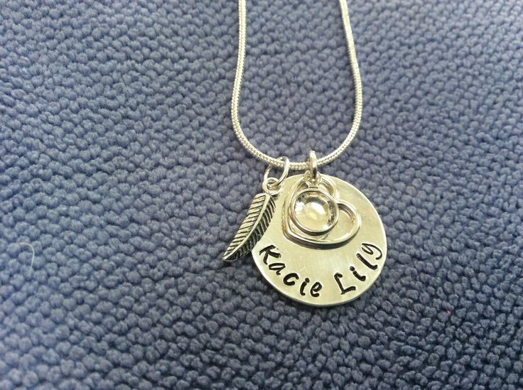 Personalised silver hand stamped disc with name, open heart, crystal Swarovski birthstone (April) and silver feather €38