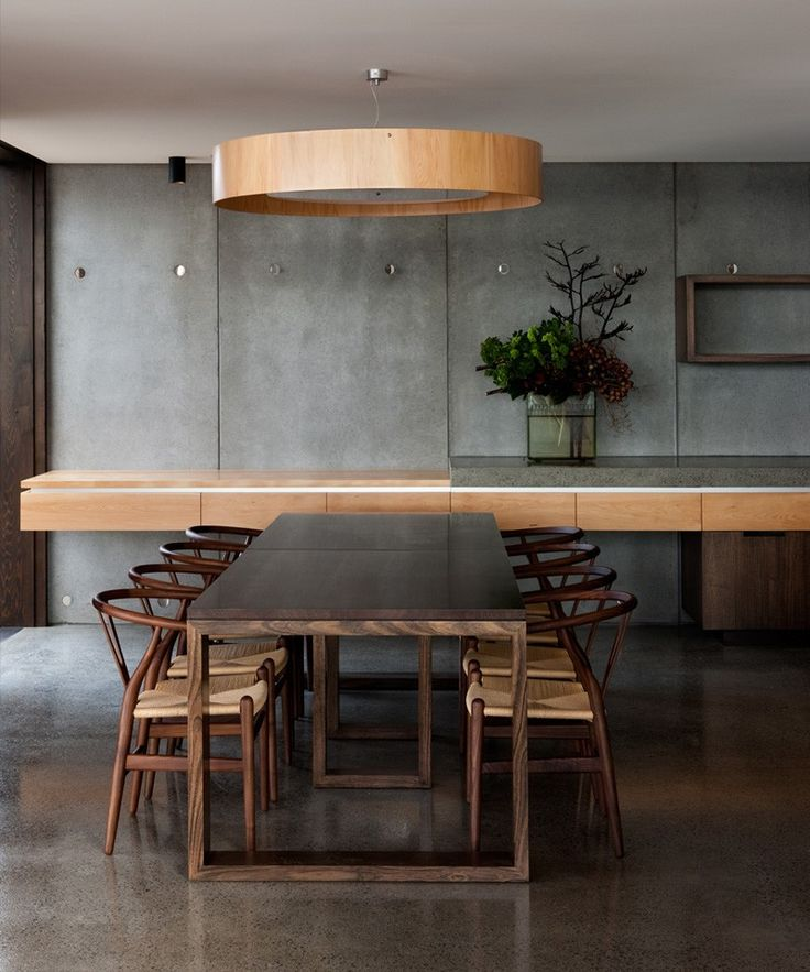 Modern Living Spaces // grey concrete floors pair well with a dark wood minimal table and classic chairs. The lighter wood and concrete counter tie it all together at this home in Hobart, Tasmania, designed by MGArchitects