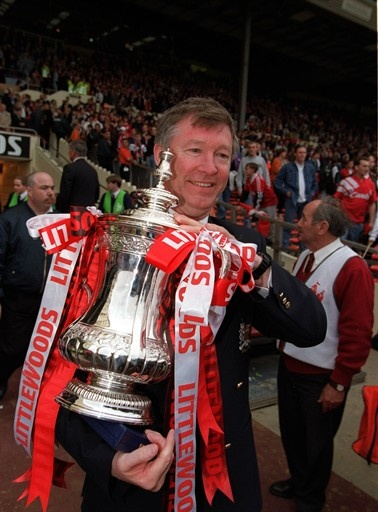Manchester United manager Alex Ferguson proudly holds the trophy after the 1996 FA Cup final