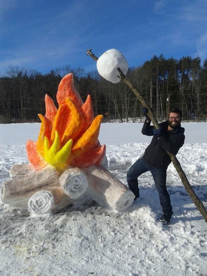 Giant fire and marshmallow snow sculpture by Schaffer Art Studio. To get the color of the flames and logs the artist used food coloring mixed with water in a spray bottle and 'spray painted' the flames and wood on.
