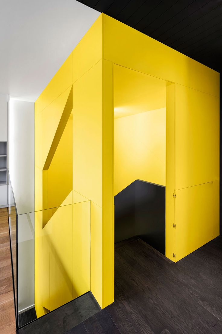 Architects used strips of black to articulate circulation throughout this house. A focal point of the interior is a black and yellow stairwell with geometric cut-outs.