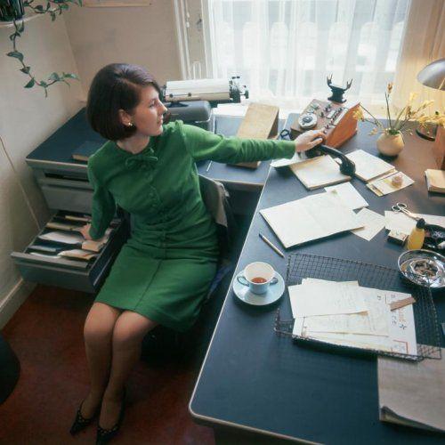 Wout van de Hoef | Secretaresse Pieneke Bakker achter haar bureau met onder andere telefoon, thee,  asbak, fresia's en draadmandje, Nederland, 1967.