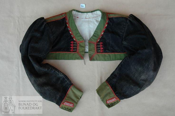"""Setesdal. Trøye med skulder -og sidesaum og falske panelsaumar på ryggen. Svart kledesliknande tøy (ser kanskje ut som det kan vere bomull renning med ull innslag). Veldig slitt. Fora med kypertvove bomull, påsydd """"oppstiving"""" av vadmål rundt erme. Brei kant av grønt klede pryda med """"løyesaum"""" langs nedkant, framkant og hals, over skuldersaum og panelsaum i ryggen. """"Løyesaum"""" og 4 knapphol på kvart framstykke. To-saumserme med rynka ermtopp, fora med kypertvove bomull. Belegg av grønt klede…"""