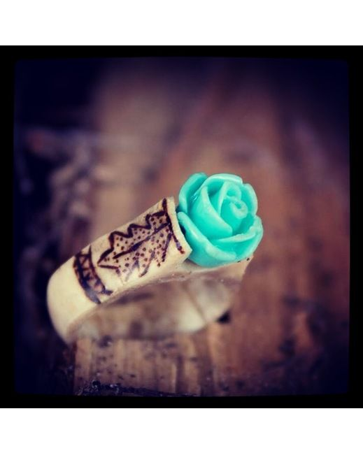 A teal resin rose sits proudly on a hand carved antler ring with hand burned leaf designs.
