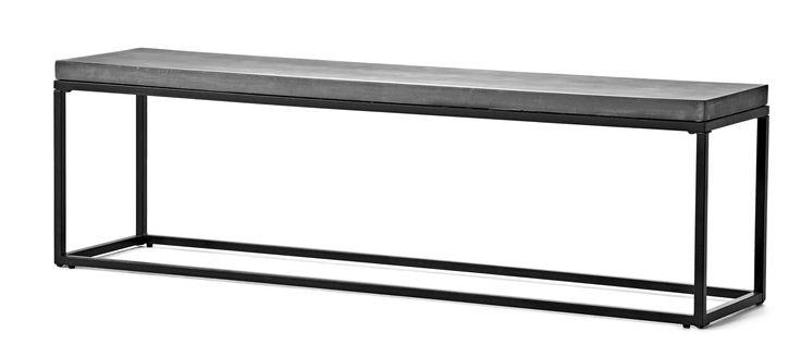 Sittbänk med skiva i komposit med betongkänsla och vaxad yta, som är lättare och mer hållbar än betong. Underrede i lackerad metall.