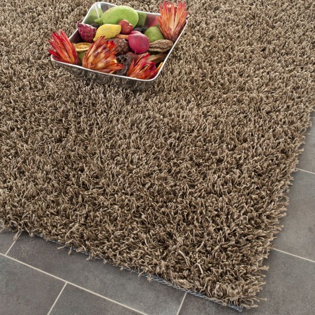 This hand-tufted polyester shag rug offers luxurious comfort and modern style. High-density polyester pile with boxed-strands peppered across features a light Brown background