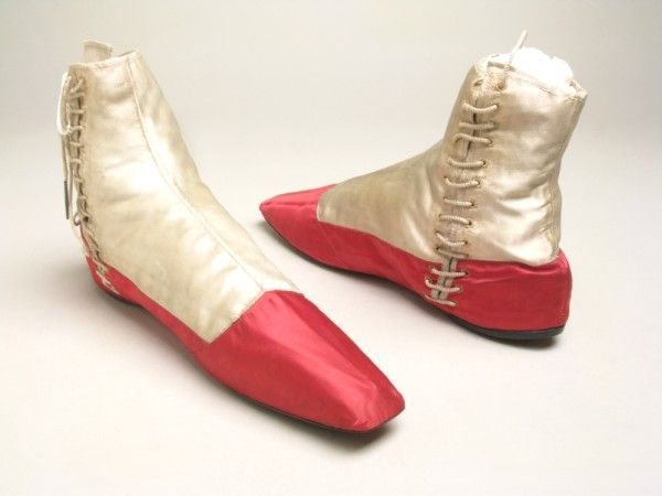 Shoes, circa 1830-50. White and cerise satin over linen.  Narrow square toes with cerise toe-caps. Side opening with white cord tagged laces. Tongue lined with cerise. Sole thickened at heel.