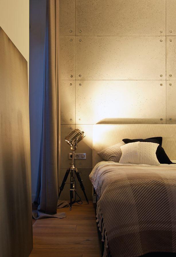 Une ambiance lumineuse très théâtrale se dégage dans cette chambre, grâce aux projecteurs type cinéma qui éclairent un haut mur de plaques de béton brut.