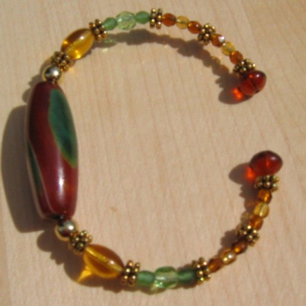 I had gone to a gem shop and found these wonderful stone beads that I thought would make great focal beads for a bracelet. I used memory wire.I mixed different fire polished beads and crystals and a few spacers. I loved the color combinations.  The end beads are glued on as I do not like the bent end that is often suggested for memory wire.