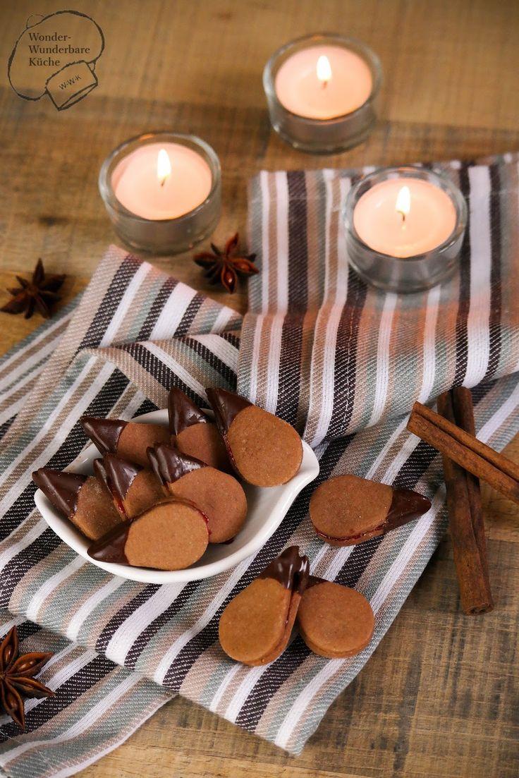 Wir starten mit der Weihnachtsbäckerei! Zart mürbe Plätzchen aus Schoko-Mürbeteig mit Zimt und Nelken, gefüllt mit einer säuerlichen Johannisbeer- Himbeermamelade. Die Spitzen der Tropfen werden in Schokolade getaucht! Der perfekte Start in den Advent.