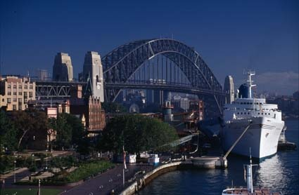 Cruise liner berthed in Sydney Harbour with Bridge in background and ferry in foreground, 1991. NAA: A6135, K18/2/91/32
