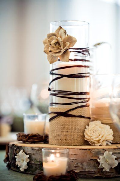 Here's a great, rustic centerpiece idea! Wood stump with a taller candle wrapped in twine, surrounded by tealights with a few paper flowers!