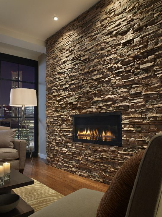 The dark stacked slate with the inset fireplace and well placed accent lighting makes me want to curl up in that end chair and read a book. Such a romantic yet strong space. Shows a great way to combine elements so that your room is inspiring, but not too feminine.